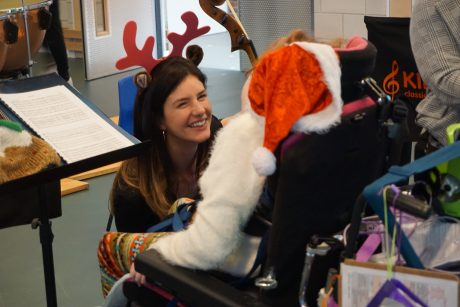 Female violinist with long brown hair in reindeer antlers kneeling in front of a child in a wheelchair wearing a santa hat. The violinist is showing the child her violin.