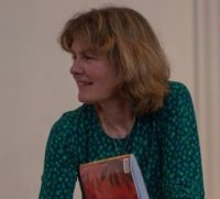 Picture of Anita Memmott in a blue and green patterned top holding a book.