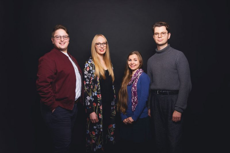 Four young composers stand in a row