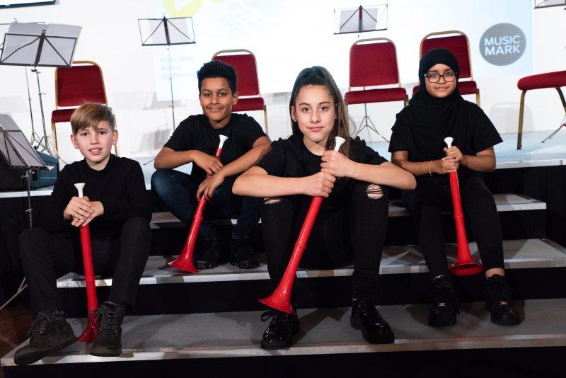 4 children sat on steps holding red pBuzz instruments.
